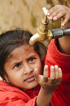 Young girl checking to see if the communal village water tap has water, as it runs dry daily, Pokhara, Nepal, Asia