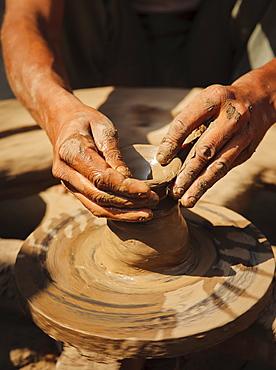 Local potter making earthenware pots on a hand driven wheel, Saijpur Ras, Gujarat, India, Asia