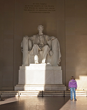 The statue of Lincoln in the Lincoln Memorial being admired by a young girl, Washington D.C., United States of America, North America
