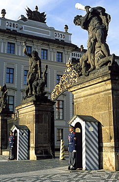 Two guards in front of the gate to Prague Castle, which has a titan statue on each of its two pillars, Hradcany, Prague, Czech Republic, Europe