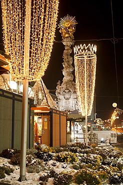 Snow-covered flowers, Christmas decorations and Baroque Trinity Column (Dreifaltigkeitssaule) at Christmas Market, Hauptplatz Square, Linz, Oberosterreich (Upper Austria), Austria, Europe