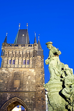 Gothic Old Town Bridge Tower and statue of St. Ivo (Bishop of Chartres) at twilight, Old Town, UNESCO World Heritage Site, Prague, Czech Republic, Europe