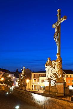 Statue of Crucified Jesus Christ on Kamenny Most, the oldest Gothic stone bridge in Czech Republic, at dusk, Pisek, Budejovicko, Czech Republic, Europe