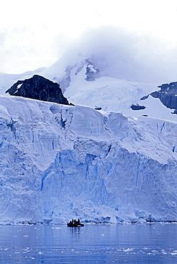 Tourists in zodiac below edge of glacier, Antarctica, Polar Regions