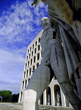 Statue with the Palazzo della Civilta di Lavoro behind, EUR (Esposizione Universale Romana), suburb planned in the 1930s during the time of Mussolini, Rome, Lazio, Italy, Europe