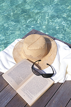 Straw hat, book and sunglasses on towel, North Male Atoll, Maldives, Indian Ocean, Asia