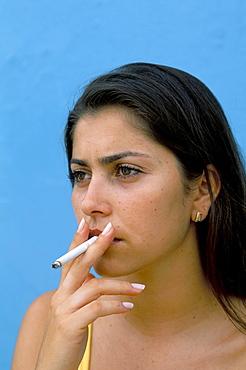 Portrait of a young woman smoking a cigarette, Genipabu (Natal), Rio Grande do Norte state, Brazil, South America