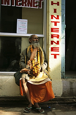 Sadhu (Hindu holy man) sitting outside an internet cafe, Varanasi (Benares), Uttar Pradesh state, India, Asia
