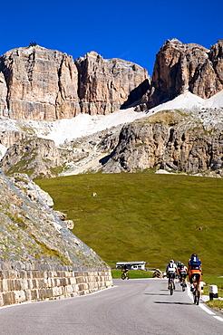 Cyclist during Pordoi pass with view on Sella mountain and  Piz Bovû, Dolomites, Fassa valley, Trentino Alto Adige, Italy, Europe