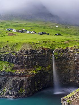The waterfall near Gasadalur, one of the landmarks of Faroe Islands. The island Vagar, part of the Faroe Islands in the North Atlantic.  Europe, Northern Europe, Denmark, Faroe Islands