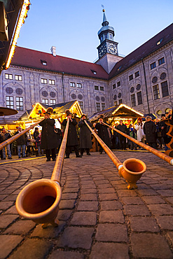 Christmas market in Munich. The alpine  Christmas Village in the Kaiserhof of the Residenz, the palace of the bavarian kings. Concert with Alpenhorn (Alphorn). Europe, Germany, Bavaria, Munich