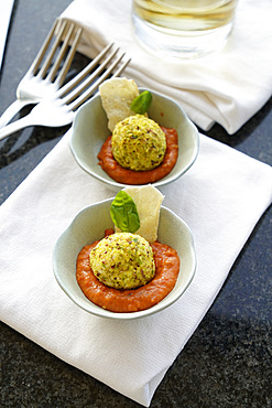 Fresh ricotta covered with chopped pistachios on an organic tomato cream