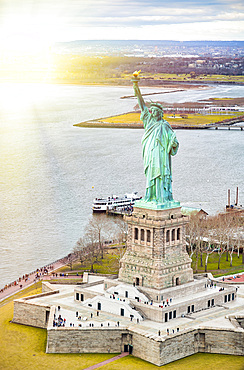 Statue of Liberty on Liberty Island and Ferry Boat with tourists, New York City.