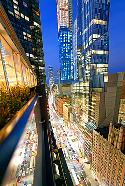 Amazing skyscrapers in Midtown Manhattan, aerial view from rooftop with traffic reflections on the buildings at night.