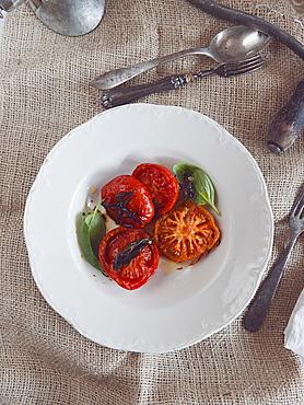 Roasted tomatoes with fresh basil, Italy, Europe