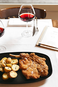 Cotoletta Milanese cooked by Restaurant Brunello in Milano served with baked french potatoes and tomatoes salad and a glass of mild red wine.