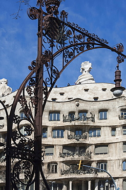 A wrought iron lamp frames La Pedrera (Casa Mila), an apartment block designed by Antonio Gaudi, UNESCO World Heritage Site, Passeig de Gracia, Barcelona, Catalunya, Spain, Europe