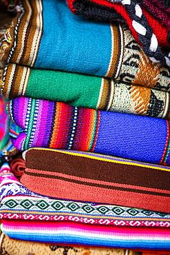 Colorful carpets made of llama and alpaca wool for sale at San Pedro market, Cuzco, Peru.