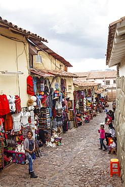 Shops along the the Inca wall at Hathunrumiyoq Street, las piedras del los 12 angulos (the stone of the 12 angles), Cuzco, Peru, South America