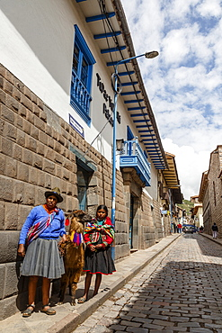 Women with traditional dress along Tupac Yupanqui Palace Hotel wall with its gray andesite blocks on San Agustin street, Cuzco, UNESCO World Heritage Site, Peru, South America