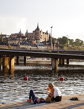 Couple sitting by the water overlooking Sodermalm and Riddarholmen, Stockholm, Sweden, Scandinavia, Europe