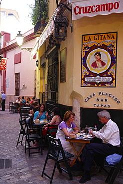 People sitting at a tapas bar in Barrio Santa Cruz, Seville, Andalucia, Spain, Europe