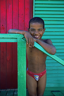 Young boy stands by colourfully painted Victorian bathing hut in False Bay, Cape Town, South Africa, Africa