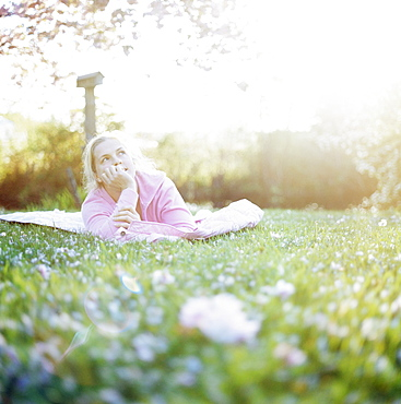 Woman relaxing on lawn surrounded by cherry blossom, Washington State, USA
