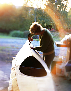 Boat builder working on a stich and glue kayak, Washington State, USA
