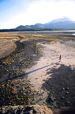 Man walking on dry lake bed with Llaima Volcano in distance, Conguillio National Park, Chile, South America