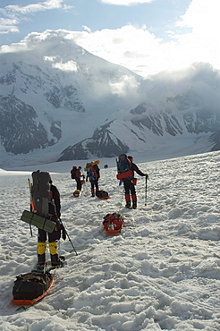 Hikers break with Mount Foraker on the left and Mount Crosson on the right, in distance, Denali National Park, Alaska, United States of America, North America