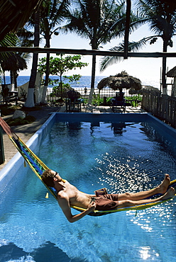 Tourist in hammock relaxing over pool, Monterico, Guatemala, Central America