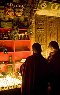 Monks light butter lamps on an auspicious night, watched by two fearsome masks, Boudha stupa, Bodhnath, Kathmandu, Nepal.