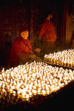 Monks light butter lamps on an auspicious night, Boudha stupa, Bodhnath, Kathmandu, Nepal, Asia