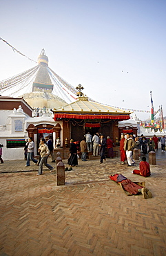 A Buddhist prostrates at dawn before the main entrance to Kathmandu's Tibetan stupa called Boudha (Boudhanath) (Bodhnath), Kathmandu, UNESCO World Heritage Site, Nepal, Asia
