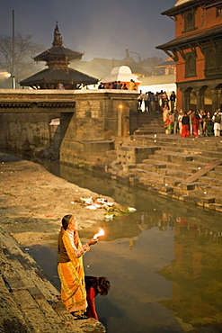 Two women making offerings (puja) before dawn by the Bagmati river, outside the Shiva temple during the Hindu festival of Shivaratri, Pashupatinath, Kathmandu, Nepal, Asia