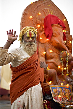Holy man raises a hand in front of a Ganesh statue draped in fairy lights at the Hindu festival of Shivaratri, Pashupatinath, Kathmandu, Nepal, Asia