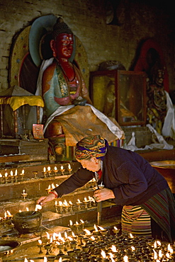 Old woman lighting butter lamps in a small temple on the north side of Boudha or Bodhnath stupa, Tibetan New Year (Lhosar), Kathmandu, Nepal, Asia