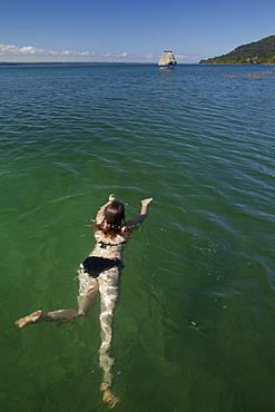 Woman swimming in Lago Peten Itza, Guatemala, Central America