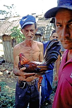 A farmer holding a fighting-cock at a cockfight in rural Pinar del Rio Province in western Cuba, Cuba