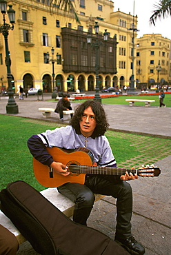 Student musician playing the guitar and performing in the Plaza de Armas, Lima, Peru