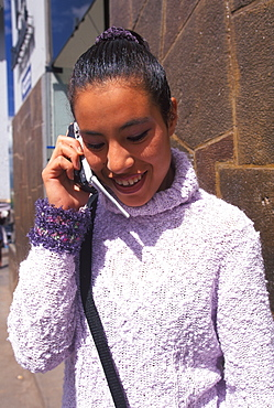 Ancient capital of the Incas a Peruvian student using a cel phone in the center of the city near the university, Cuzco, Highlands, Peru