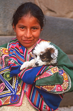 Ancient capital of the Incas portrait of a young Quechua Indian girl in traditional dress with a puppy carried in her shawl, Cuzco, Highlands, Peru