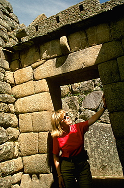 Machu Picchu a visitor examines the finely cut stones that form the entrance to the precinct of the Temple of the Sun, Highlands, Peru