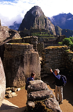 Machu Picchu the Temple of the Sun with the site's most perfect stonework visitors view grotto called the Royal Tomb below the temple, Highlands, Peru
