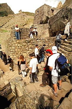 Machu Picchu visitors on steps next to the fountains which are actually sixteen small waterfalls in a series of baths used ritually, Highlands, Peru