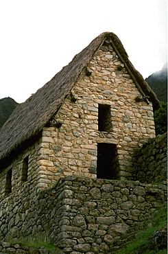 Machu Picchu a house showing construction details, especially stone protuberances used for tying down thatch roofs, Highlands, Peru