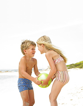 Boy and girl (6-8) on beach playing with ball