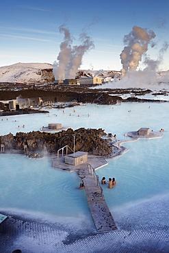 People relaxing in Blue Lagoon geothermal spa, Svartsengi Geothermal Power Station in the distance, Grindavik, Reykjanes Peninsula, Iceland, Polar Regions