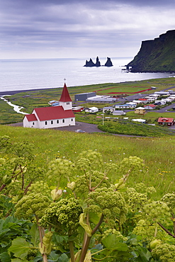 Church and village of Vik (Vik a Myrdal) and Reynisdrangar sea stacks in the distance, south coast of Iceland (Sudurland), Iceland, Polar Regions